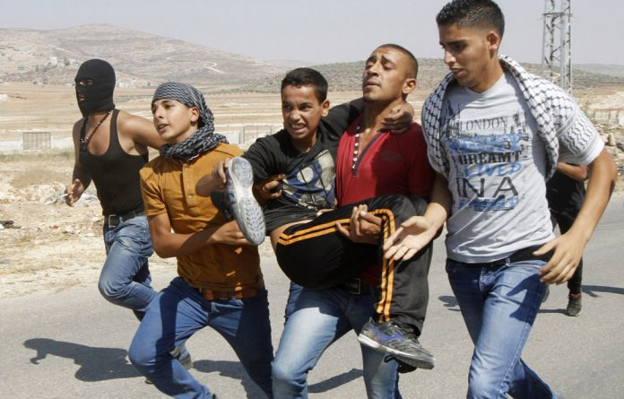 Palestinian protesters carry a wounded youth during clashes with Israeli soldiers on August 15 2014.