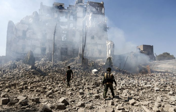 Houthi rebels inspect the damage after an air strike by the Saudi-led coalition hit the presidential palace in Yemen in 2017. Devastation is wrought in Yemen by the coalition with some of the munitions supplied by South Africa.