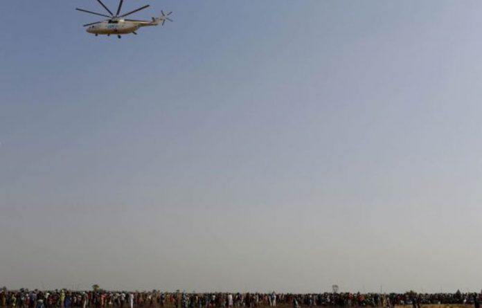 A United Nations World Food Programme helicopter flies over people waiting to be registered for food distribution in Thonyor