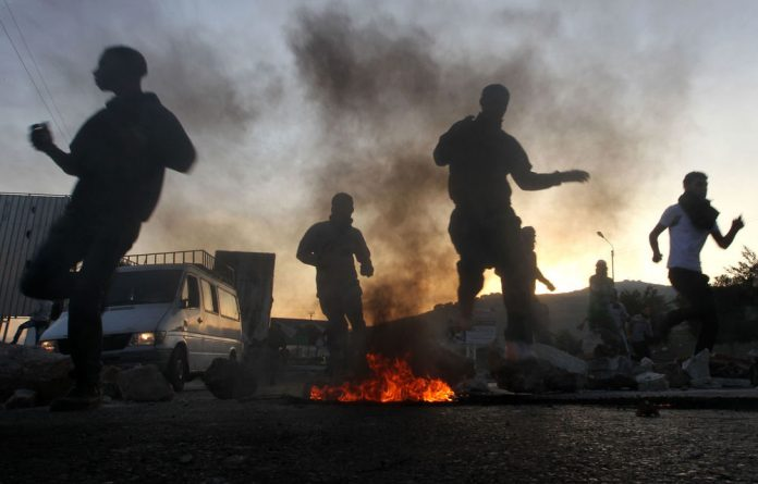Palestinian stone throwers run for cover during clashes with Israeli security forces in the West Bank city of Nablus