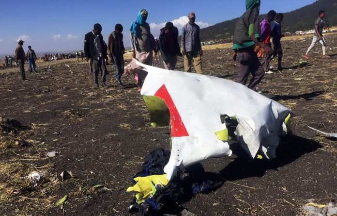 People walk past a part of the wreckage at the scene of the Ethiopian Airlines Flight ET 302 plane crash