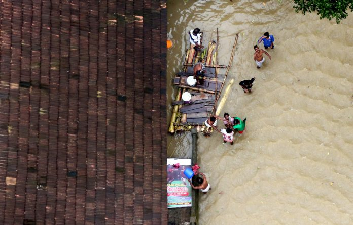 People wait for aid next to makeshift raft at a flooded area in the southern state of Kerala.