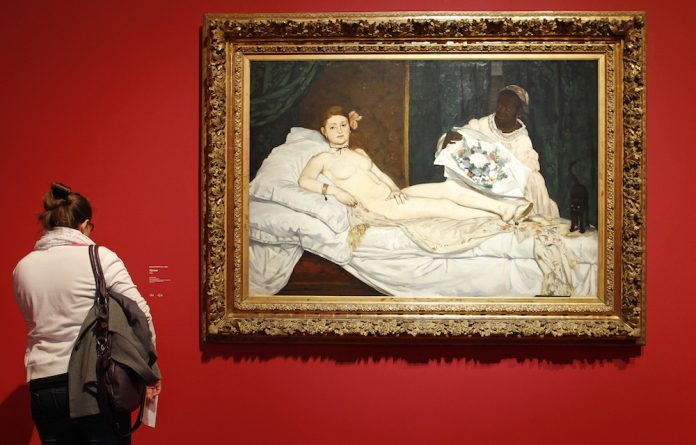 Visitors look at Edouard Manet's painting the Olympia at Paris's Musée d'Orsay.