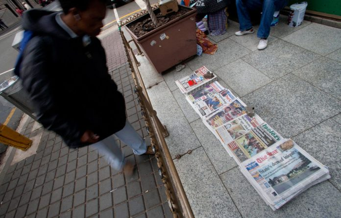 A man browses the morning newspapers.
