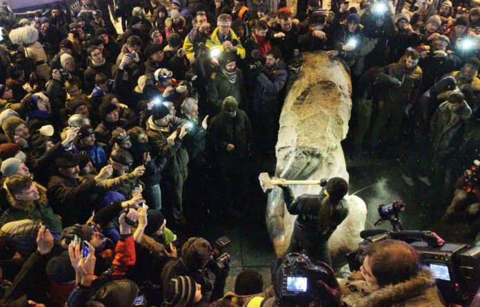 A protester breaks apart a statue of Lenin after it was pulled down during a mass rally called 'The March of a Million' in Kiev's Independence Square on December 8.