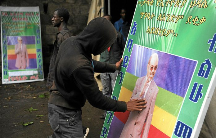 An Ethiopian man prays as he holds a poster of the late Ethiopian prime minister Meles Zenawi.