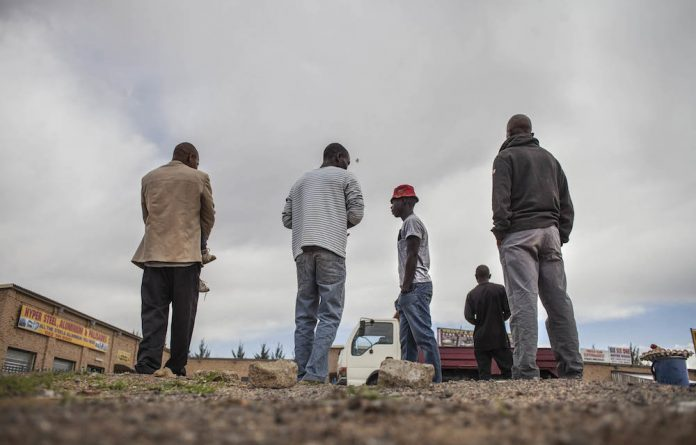 Unemployed men loiter in a vacant lot.