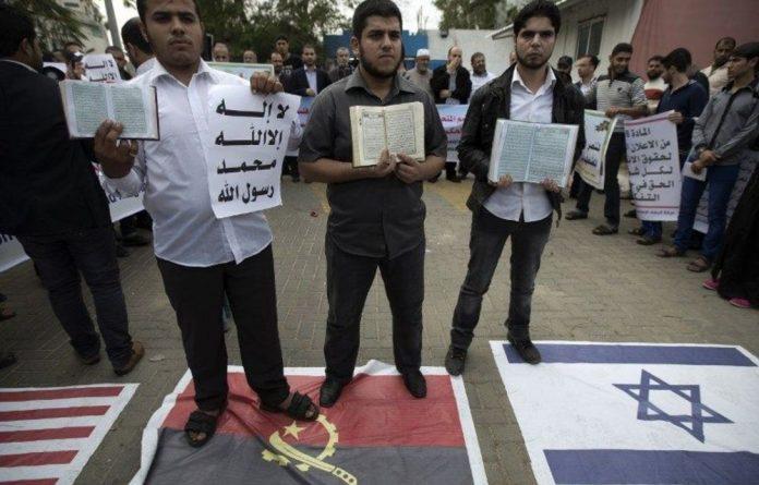 People hold copies of the Koran