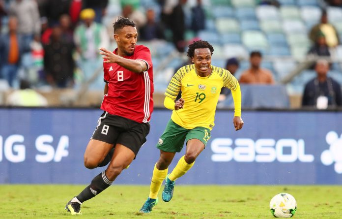 Percy Tau of South Africa and Sand Masaud MMasaud of Libya race for the ball ina2019 Africa Cup of Nations qualifying match.Coach Stuart Baxter is relying on the on-form Tau and Dino Ndlovu to score for South Africa.