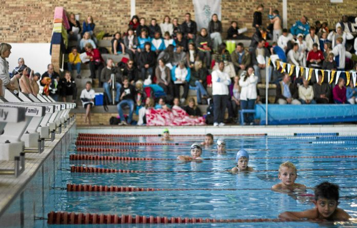 Swimmers wait for the signal to leave the pool after a race.