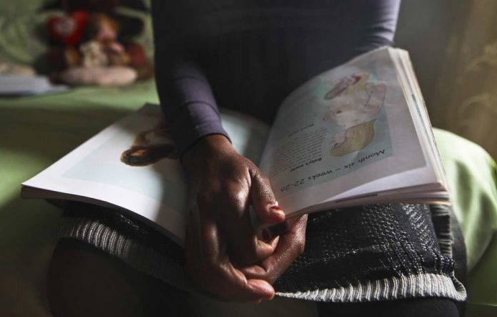 A pregnant woman reads up about childcare.