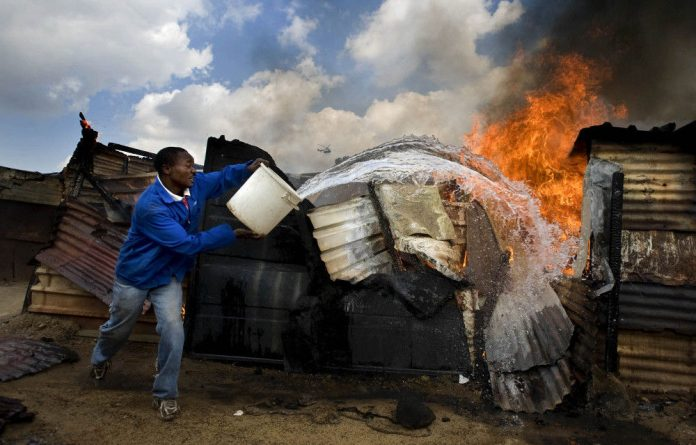 A man tries to extinguish a fire in his shack following violent and deadly xenophobic attacks at Ramaphosaville in April last year.