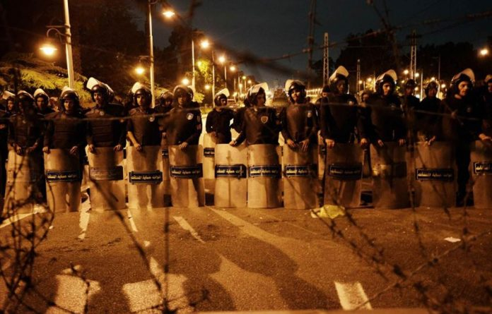 Egyptian riot police stand behind barbwire as thousands of demonstrators march to the presidential palace to protest against the new constitution and President Mohamed Morsi's decrees.