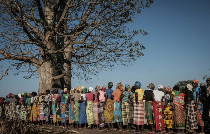 Aftermath: People affected by Cyclone Idai are now largely reliant on donor aid for short-term food needs. Here women queue for relief packages in Estaquinha