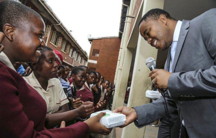 Education MEC Mthandeni Dlungwana hands sanitary towels to girls at Lamontville High School.