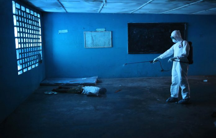 A Liberian health worker disinfects a corpse after the man died in a classroom now used as an Ebola isolation ward in Monrovia