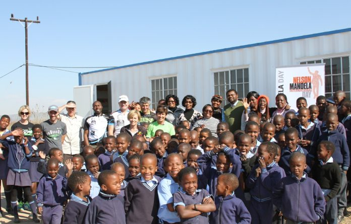 Children and staff of the Mahlubimangwe Primary School in KwaZulu-Natal together with members of the Mandela Library Project in front of the school's container library.