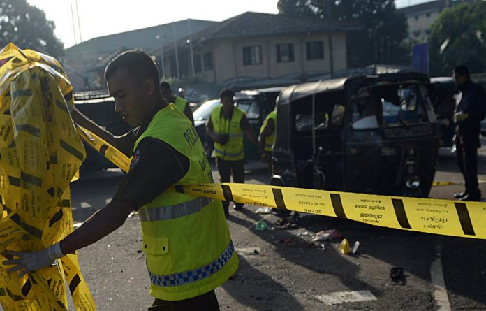 Security personnel examine a three-wheel taxi allegedly used by inmates to escape from the Welika maximum prison in Colombo.