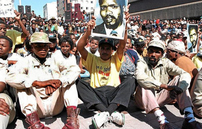 A supporter hoists an image of Steve Biko on the 20th anniversary of his death