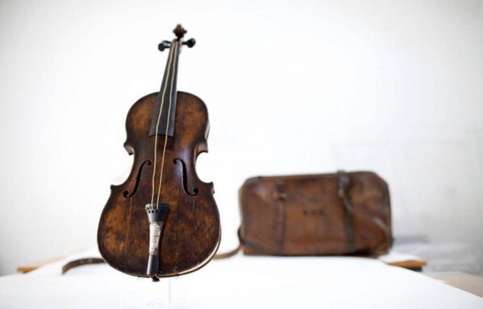 The violin played by bandmaster Wallace Hartley during the final moments before the sinking of the Titanic is displayed with a leather carrying case initialed W H H.