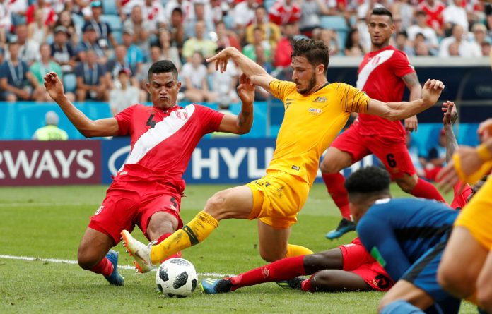 Australia's Mathew Leckie in action with Peru's Anderson Santamaria and Christian Ramos.