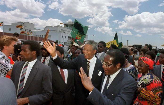 Opposites: Nelson Mandela is seen here with Zimbabwean President Robert Mugabe in Harare in March 1990