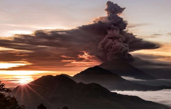 The Mount Agung volcano is seen spewing smoke and ash in Bali. About 25