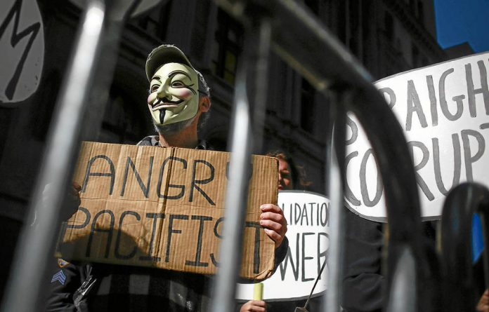 No joke: Occupy Wall Street activists protest against capitalist corruption.