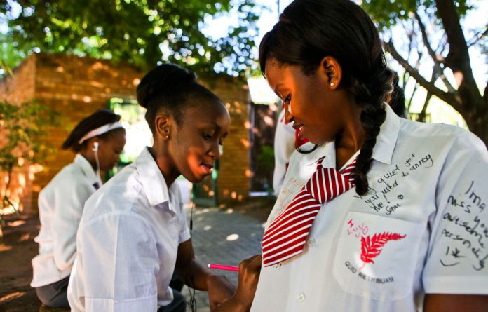 Matric pupils from Ferndale High School sign each others' shirts after writing their final exam.