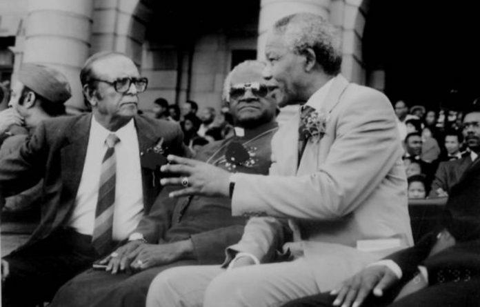 Motala and Archbishop Emeritus Desmond Tutu listen to Nelson Mandela.
