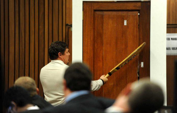 Police forensic expert Colonel Johannes Vermeulen hits the door with a cricket bat in a re-enactment of how Oscar Pistorius broke down the door of the toilet.