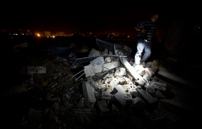 A Palestinian cameraman trudges over destruction following an Israel airstrike in Gaza City on Thursday.