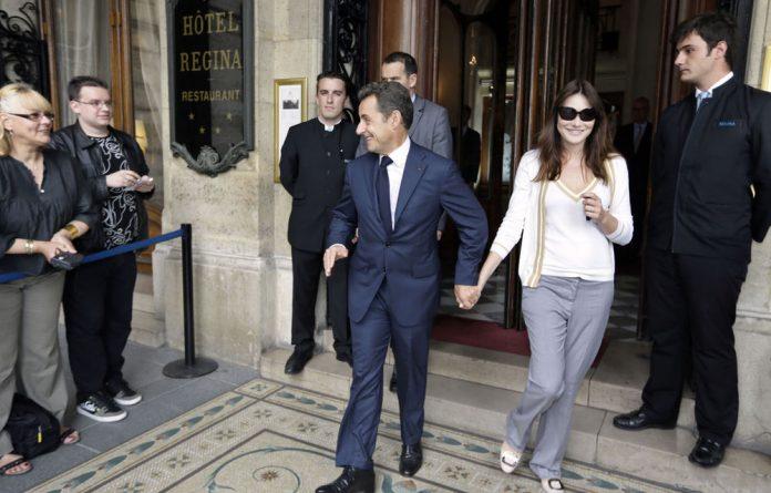 Former French president Nicolas Sarkozy and his wife Carla Bruni-Sarkozy leave the Regina Hotel in Paris.