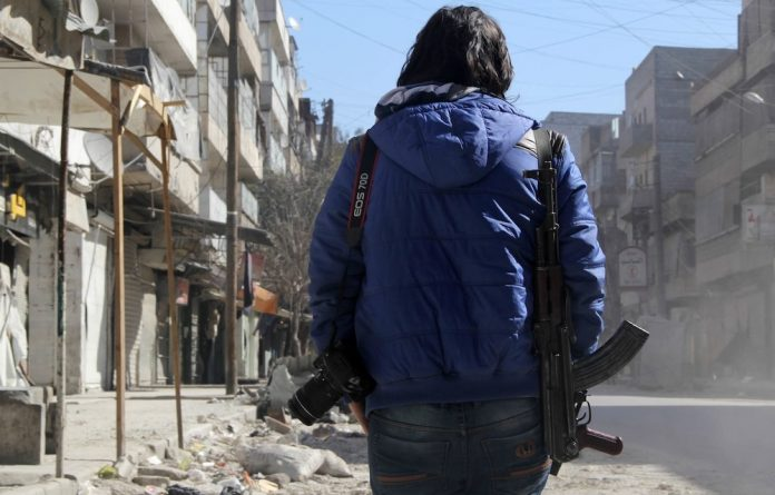 Shooting conflict: A Syrian journalist in Aleppo carries a camera and a gun
