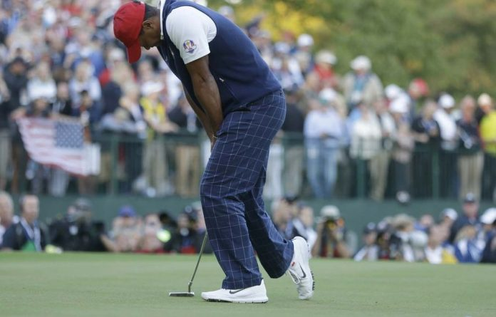 USA's Tiger Woods reacts after missing a birdie putt on the 18th hole to lose a four-ball match at the Ryder Cup PGA at the Medinah Country Club in Medinah