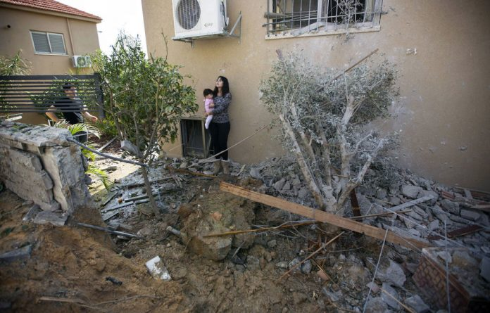 An Israeli woman holds a baby as she stands in the garden of her damaged home after it was hit by a rocket launched by Palestinian militants from the Gaza Strip in Beer Sheva on November 20.