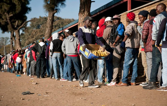 Immigrants queue from the early hours of the morning in Marabastad in downtown Pretoria to apply or reapply for their asylum permits.