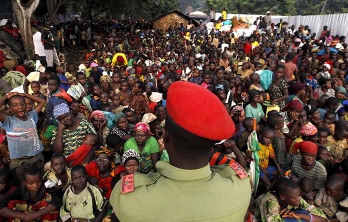 A Tanzanian policeman watches over Burundian refugees on the shores of Lake Tanganyika in Western Tanzania.