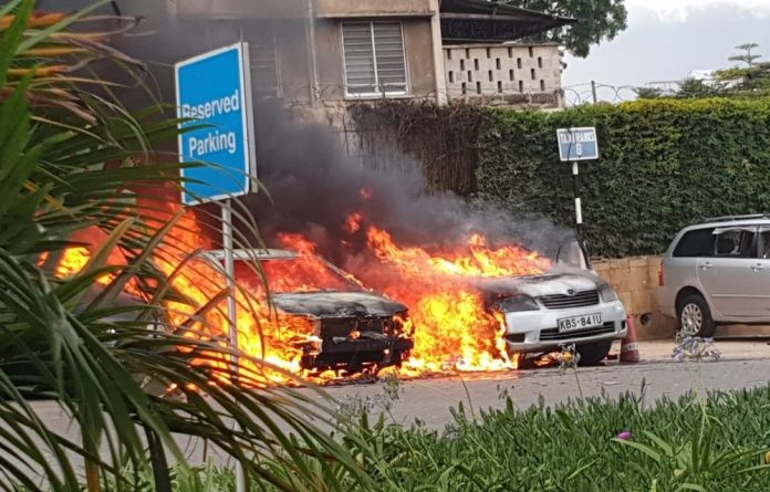 Flames and plumes of black smoke billowed into the sky from the parking lot of the compound where several vehicles were on fire