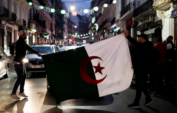 People celebrate on the streets of Algiers after President Abdelaziz Bouteflika announced he will not run for a fifth term.