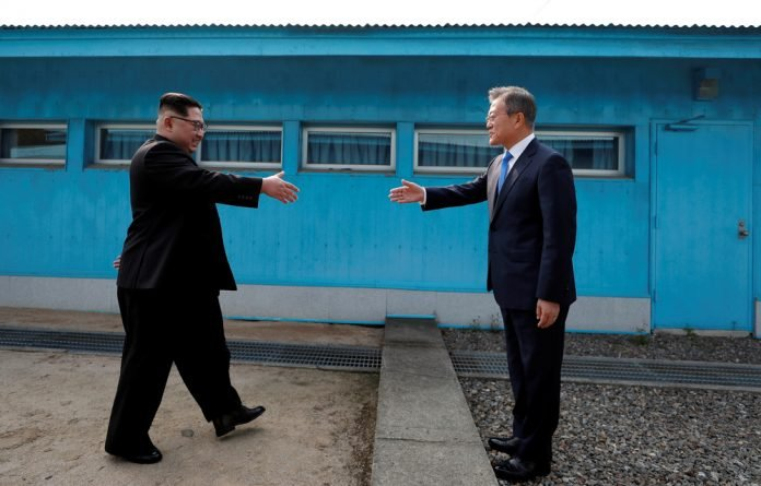 South Korean President Moon Jae-in and North Korean leader Kim Jong-un shake hands at the truce village of Panmunjom inside the demilitarized zone separating the two Koreas