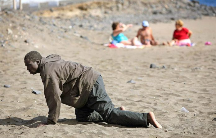 A refugee crawls to sanctuary after his makeshift boat arrived at the Gran Tarajal beach in Spain's Canary Island of Fuerteventura.