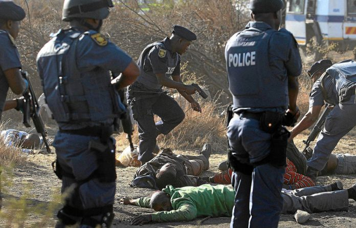 Police surround striking miners after opening fire on a crowd at the Lonmin Platinum Mine.