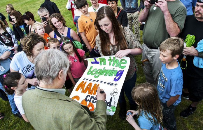 Author Richard Dawkins signs a poster during the