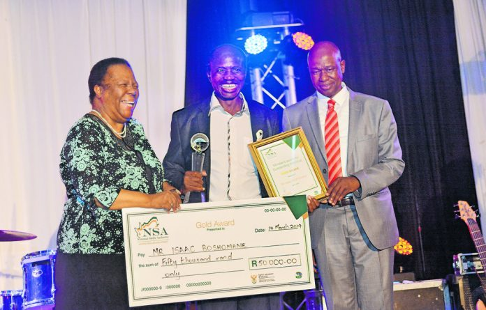Isaac Boshomane receive a prize from Minister of Higher Education Naledi Pandor