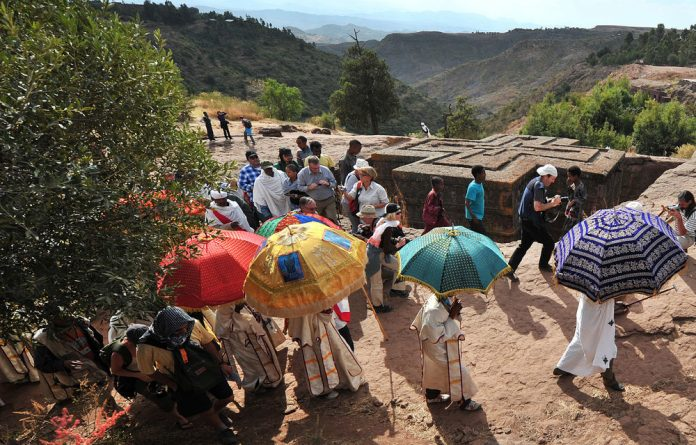 Religious leaders conducting ceremonies at the historic Lalibela site are closely tracked by camera-clicking visitors.