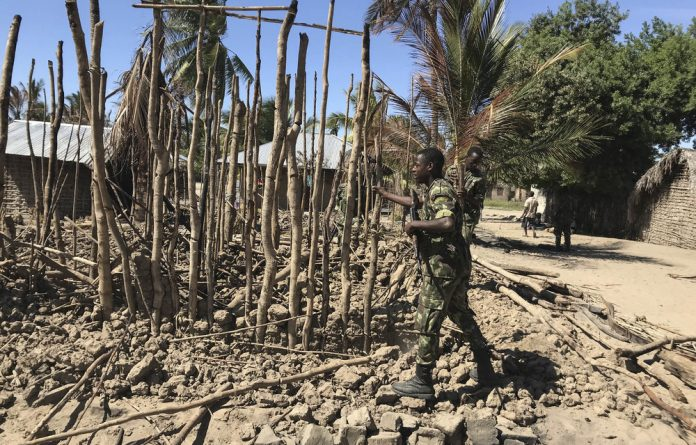 Mozambican soldiers dismantle a structure that was torched by attackers so it can be rebuilt as shelter for people fleeing the recent attacks in Naunde