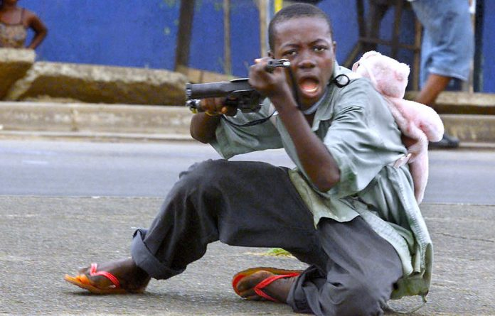 A child soldier wearing a teddy bear backpack in Monrovia