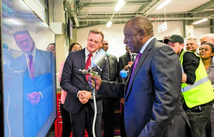 Markus Schäfer of Mercedes-Benz Cars shows South Africa President Cyril Ramaphosa the virtual painting training station at the Mercedes-Benz Learning Academy in East London.