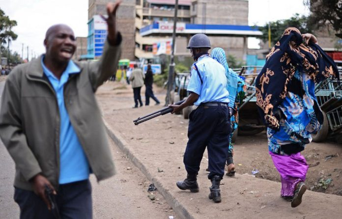 Kenyan police officers escort Somalis through Eastleigh on November 19 2012. Violence erupted after a bomb explosion the previous day